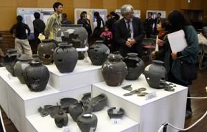 カムィヤキ陶器窯跡の遺物の修復物を鑑賞する来場者ら=16日、伊仙町伊仙