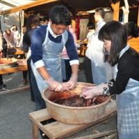 大島紬の歴史に理解を深め、テーチ木染めや泥染めを体験する参加者=15日、龍郷町の大島紬村