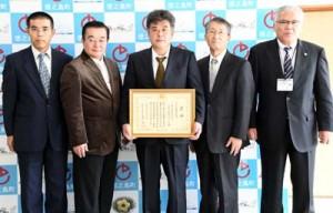 全国優良経営体表彰で農林水産省経営局長賞を受賞した永吉ファームの永吉さん(中央)=14日、徳之島町役場