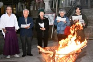 かがり火を囲んで日本復帰の歌を歌う参加者たち=25日、奄美市名瀬の高千穂神社