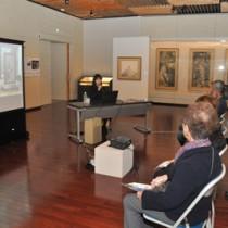 一村作品に囲まれた展示室で開かれた生誕110周年記念講演=9日、奄美市笠利町の田中一村記念美術館