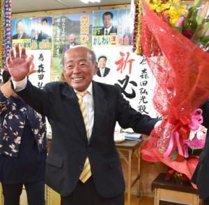 花束を手に支持者の祝福に応える森田氏=2日午後9時20分ごろ、天城町平土野