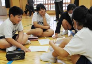 描いた絵を見せ合い、感じた事などを話し合う児童ら=20日、阿木名小中学校体育館
