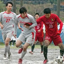 【準々決勝・Labios―龍郷クラブ】ぬかるんだグラウンドでボールを競り合う両チームの選手=9日、龍郷町中央グラウンド