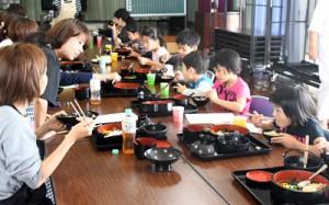 地場産食材を使って作った鶏飯を食べる子どもたち=2日、徳之島町母間の花時名公民館