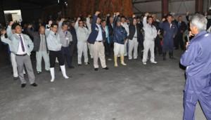 操業開始に向け、搬入出発式で頑張ろう三唱する参加者=10日、和泊町の南栄糖業構内