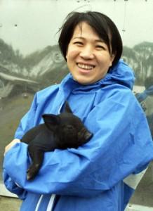 生後約10日の島豚を抱え笑顔の前田さん=2018年11月、奄美市名瀬浦上町の豚舎