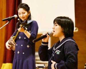 島唄の「行きゅんにゃ加那」で生徒と共演した城さん(左)=18日、瀬戸内町古仁屋