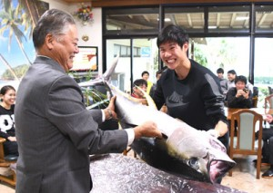 冬季合宿中の実業団チームにキハダマグロを贈った奄美群島地区漁業士会の田畑会長(左)=17日、天城町与名間