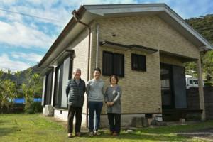 民泊施設「GAMA屋」をオープンさせた「いもーれ秋名」の村上さん(写真中央)=10日、龍郷町