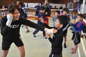 互いの肩に素早くタッチし合うゲームで、子どもたちにボクシングの動作を教える吉田選手(左)