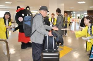 到着客にシマ博パンフレットを手渡す観光関係者=18日、奄美空港