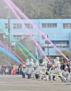 鮮やかに色付けされた水を放つ消防団員ら=6日、奄美市名瀬の伊津部小学校校庭
