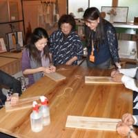 講師と英語で会話のやり取りをしながら芭蕉糸のミサンガ作りを体験する研修参加者=14日、知名町の沖永良部芭蕉布会館