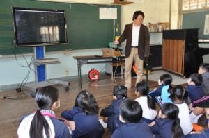 映像を駆使し、宇宙の広大さを伝える梅本さん=25日、加計呂麻島の伊子茂小中学校