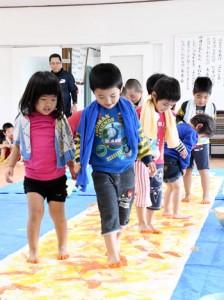布の上を歩き、足跡をつけてオリジナルアートづくりを体験する園児ら=11日、伊仙町犬田布