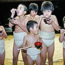 練習後、ぜんざいを頬張る子どもたち=11日、奄美市名瀬
