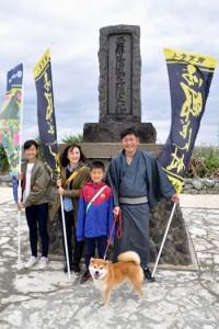 住民の協力のもと、ゆかりの地で西郷に扮し、記念撮影する観光客=2018年12月30日、和泊町の伊延港