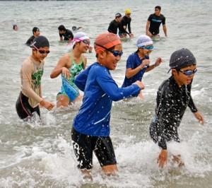 寒中水泳に挑む参加者ら=1日、奄美市名瀬の朝仁海岸