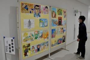 役場新庁舎1階通路に展示された児童生徒の絵画入賞作品=10日、和泊町