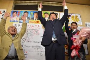 初当選を果たし万歳三唱する元山公知氏(中央)=20日午後9時ごろ、宇検村湯湾