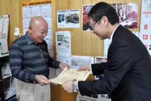 「九州農政局ディスカバー農山漁村の宝」の選定証を受け取った沖永良部きのこの今井社長(左)=23日、和泊町
