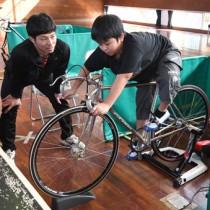 競技用自転車に乗る参加者と指導する新納選手=13日、奄美市名瀬