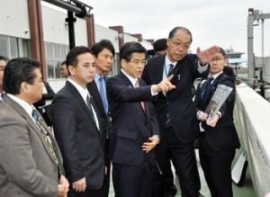 名瀬港の整備状況などについて説明を受ける石井国交相(中央手前)=6日、奄美市の名瀬港フェリーターミナル