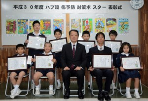 奄美大島会場の表彰式で記念撮影する受賞者8人と松本支庁長(前列中央)=26日、県大島支庁