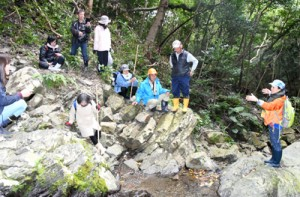「あい山の滝」について解説する永田さん(右)とプレツアー参加者=26日、徳之島町山