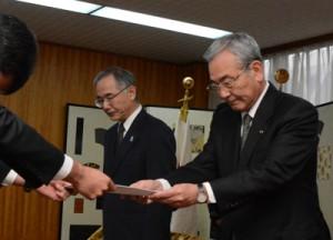 男子生徒の父親から要望書を受け取る朝山市長(右)=16日、奄美市名瀬