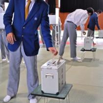 模擬投票で投票箱に一票を投じる生徒たち=29日、沖永良部高校