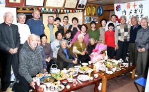110歳の誕生会で花束を手にする内メギリさんを囲む親族ら=27日、徳之島町亀徳