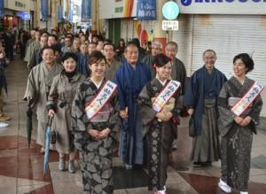 大島紬姿で商店街を練り歩き紬の魅力をPRする参加者=5日、奄美市名瀬