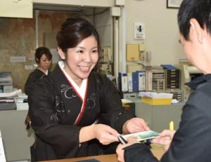 本場奄美大島紬姿で接客に当たる女性職員=4日、奄美市名瀬