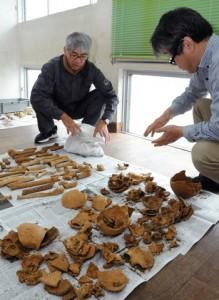 出土した人骨を分析する(右から)竹中教授と鼎学芸員=24日、瀬戸内町埋蔵文化財センター