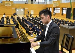 講演の合間にピアノ演奏も披露した松元陸さん=25日、金久中学校
