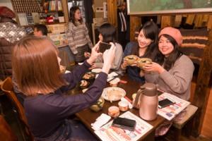 奄美の郷土料理「鶏飯」をスマートホンで撮影し、SNSで発信するインフルエンサーの女性ら=奄美料理専門店「土濱笑店」