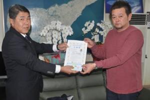 今井町長から入学準備支援金の引換券を受け取る前田さん(右)=5日、知名町役場