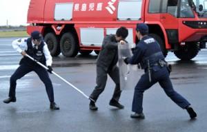 訓練で、制限区域内に侵入した不審者を取り押さえる警察官=7日、和泊町の沖永良部空港