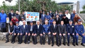 密航・密輸・密漁防止などを呼び掛ける看板を設置した関係機関のメンバー=15日、知名町のウジジ浜