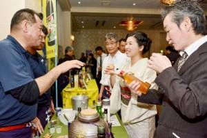 黒糖焼酎の試飲ブースで飲み比べを楽しむ参加者=22日、奄美市名瀬