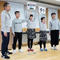 紙芝居で「方言しりとり」を披露した田代さん家族=10日、東京都立川市の国立国語研究所