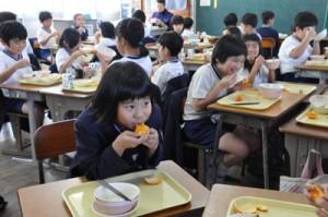 提供されたタンカンを頬張る児童=7日、奄美市名瀬の伊津部小