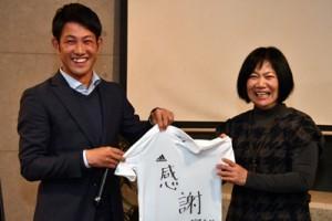 母親の明美さんに「感謝」と書いたシャツを手渡す向井さん=23日、奄美市名瀬