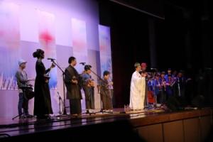 コンサートで喜界島の唄者と共演する朝崎郁恵さん(白い衣装)=23日、喜界町体育館