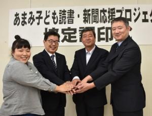 「あまみ子ども読書・新聞応援プロジェクト」に関する協定を締結した4者の代表ら=7日、奄美市名瀬