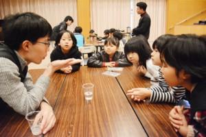 講師の学生と科学実験の結果を見詰める児童=17日、宇検村の元気の出る館