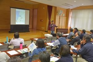 奄美トレイルのコース案の紹介があった全体交流会と講演したマイケル・ミレイさん(下)=12日、奄美市名瀬