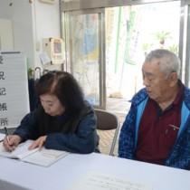 県大島支庁に設置された慶祝記帳所で記帳する夫婦=24日、県大島支庁